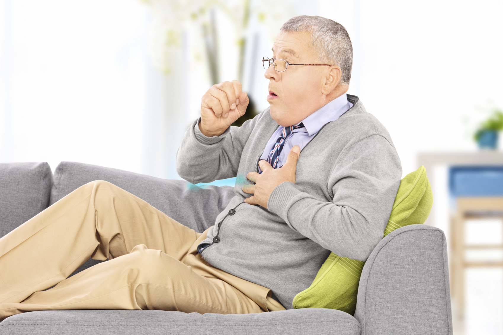 Man with COPD coughing on his couch