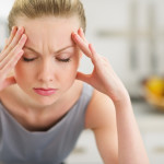 Woman suffering an intense migraine attack