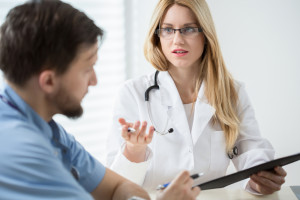 Doctor discusses genital herpes treatment with man